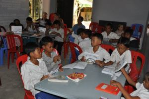 Cambodian students learning Bible stories and English through contextual coloring books.