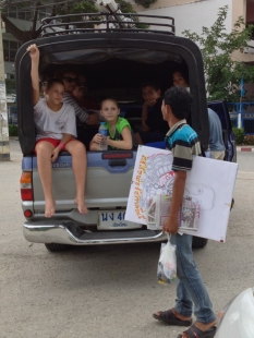 This guy was walking by as we were stopped in a parking lot trying to find the church. He was an artist. He spoke very good English, and we all had a great conversation with hiim. He gave the girls some coloring pens. The portrait he is carrying was a picture he was drawing of Rama 5 (King of Thailand).