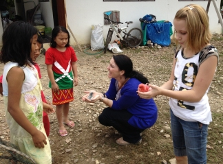 Justine getting to know new Kachin (Burmese) friends with blue and pink baby chicks.