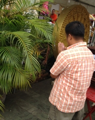 A man praying to a tree at the temple. He has 20 baht in his hands.