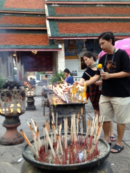 Buddhist believeers lighting candles at the temple.