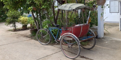 """A tuk tuk. We don't see these """"man-powered"""" tuk tuks in Chiang Mai much anymore. They are all motorized in the city. But we saw hundreds in Lamphun. In fact, we didn't see any motorized tuk tuks, but we did see lots of skinny men with huge calf muscles peddling people around town!"""