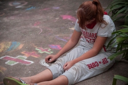 Jaynee creating sidewalk art at a recent barbecue with students.
